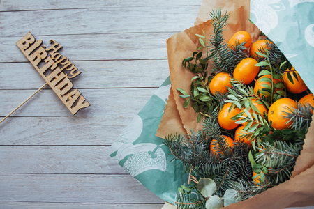 bouquet of mandarin and green branches on a white wooden background