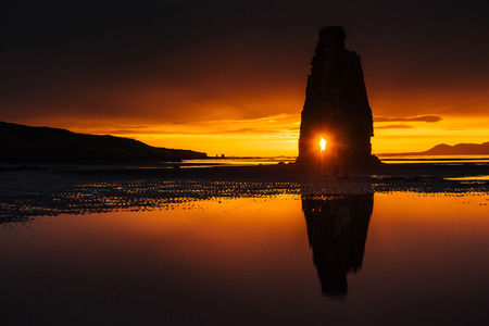 after midnight: Hvitserkur 15 m height. Is a spectacular rock in the sea on the Northern coast of Iceland. On this photo Hvitserkur reflects in the sea water after the midnight sunset