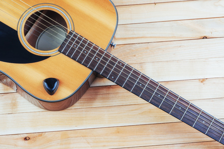 Photography classical guitar on a light brown background.