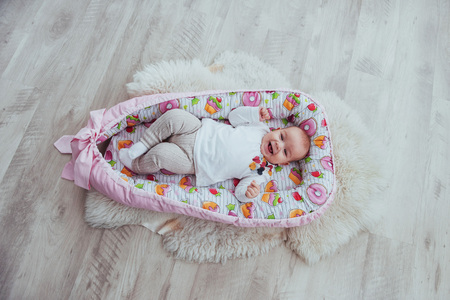 Photo charming newborn baby in a pink cradle. In good light studio