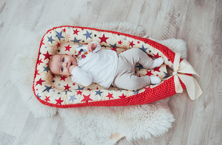 Photo charming newborn baby in a red cradle. In good light studio