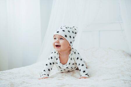 Pasgeboren baby gekleed in een wit pak en zwarte sterren is een wit zacht bed in de studio.