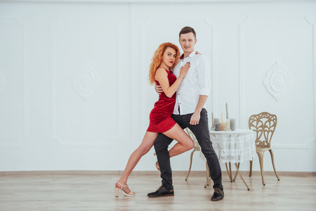 Young beautiful woman in a red dress and a man dancing, isolated on a white background in the studio