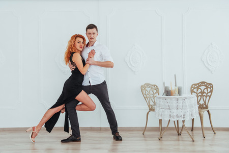 Young beautiful woman in a black dress and a man in white shirt dancing. Isolated on white background.