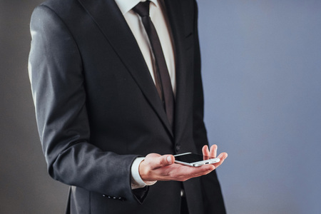 Businessman with a phone in his hand. A student in a suit on a dark background Stock Photo - 74539439