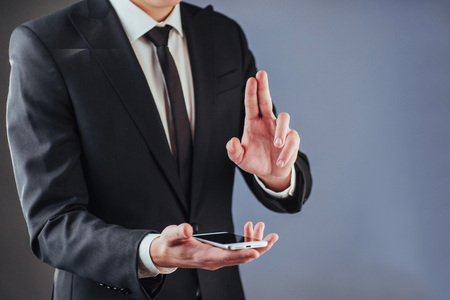 Businessman with a phone in his hand. A student in a suit on a dark background Stock Photo