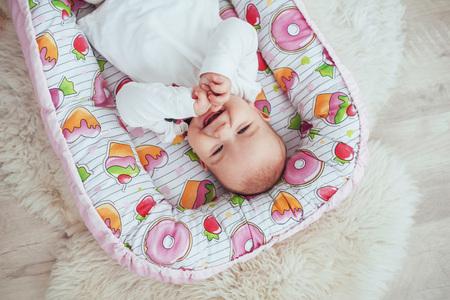 Photo charming newborn baby in a pink cradle. In good light studio