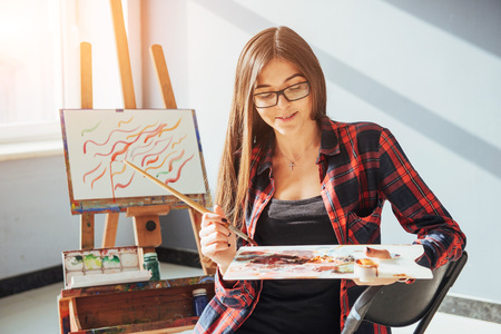 かなりかわいい女の子アーティスト塗料イーゼルにキャンバスの絵画油彩です。太陽の光が窓から壊します。 写真素材 - 74613153