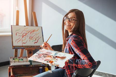かなりかわいい女の子アーティスト塗料イーゼルにキャンバスの絵画油彩です。太陽の光が窓から壊します。 写真素材 - 74613152