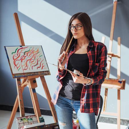 かなりかわいい女の子アーティスト塗料イーゼルにキャンバスの絵画油彩です。太陽の光が窓から壊します。 写真素材 - 74629230