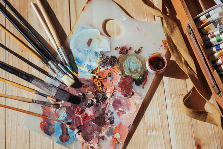 The artists palette. Colored oil paints over a pallete on a table