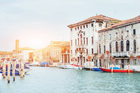 Green water channel with gondolas and colorful facades of old medieval buildings in the sun in Venice, Italy