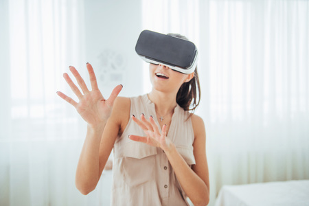 Happy woman gets experience of using VR-glasses virtual reality headset in a bright studio