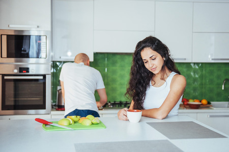 Happy young couple having coffee in the kitchen