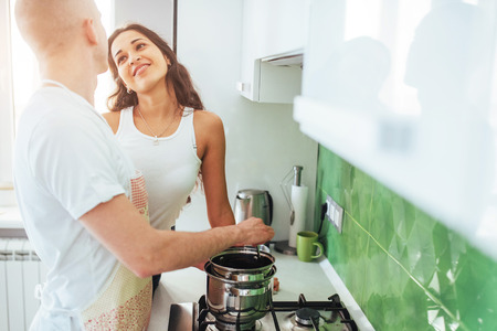 Happy young couple preparing on the stove Reklamní fotografie