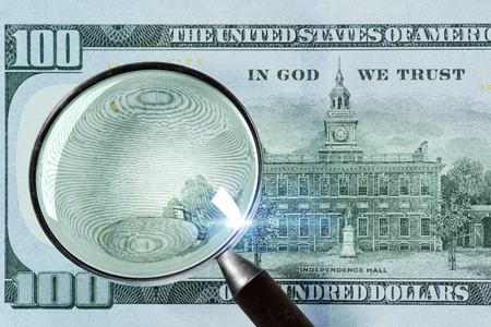 100 US Dollar under magnifying glass. close-up