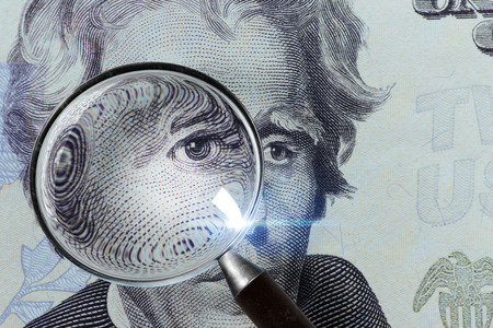 Dollar banknote under a magnifying glass is being inspected