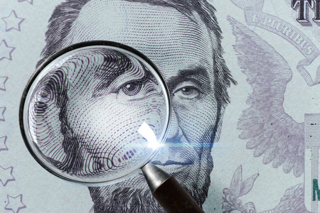 US President Abraham Lincoln face on the five dollar bill macro, 5 USD, US money close up under magnifying glass 免版税图像 - 85321640
