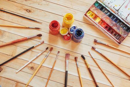 Pincel de arte y tintas de colores en latas sobre un fondo oscuro. Foto de archivo - 85392315