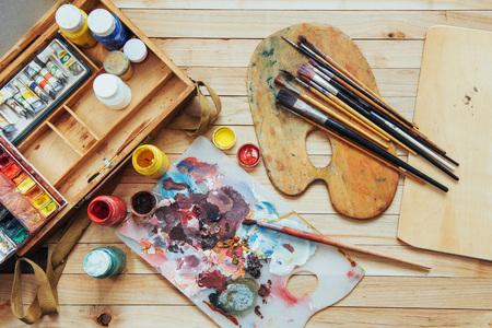 Pincel de arte y tintas de colores en latas sobre un fondo oscuro. Foto de archivo - 85392318