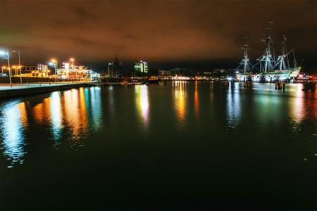 운하에있는 물 근처 건물과 보트의 야간 조명. 스톡 콘텐츠