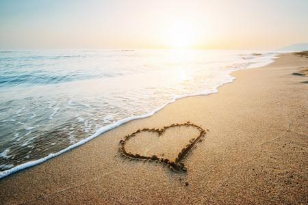 Hart tekenen op geel zand op de fantastische zonsondergang