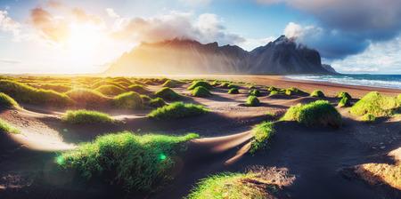 해변의 환상적인 서쪽 산과 화산 용암 모래 언덕 Stokksness