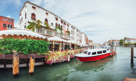 Green water channel with gondolas and colorful facades of old medieval buildings in the sun in Venice