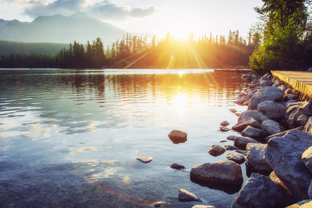 The sunrise over a lake in the park High Tatras. Shtrbske Pleso, Slovakia