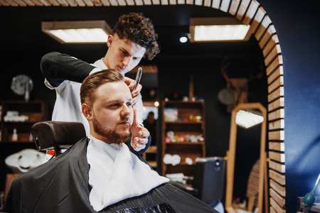 Mens hairstyling and haircutting in a barber shop or hair salon.