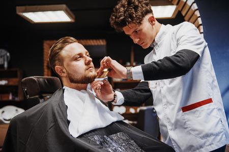 Hairstyling Mens e haircutting in un negozio di barbiere o parrucchiere. Archivio Fotografico - 85471643