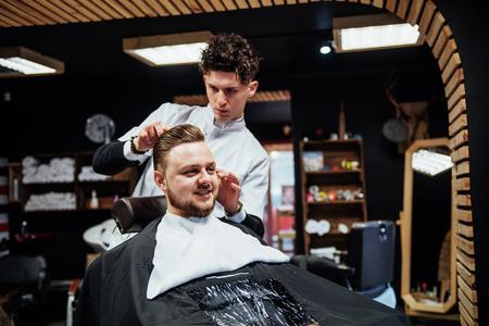 Man hairdresser doing haircut beard adult men in the mens hair salon