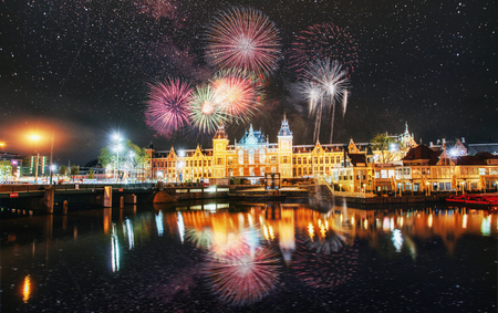 Beautiful calm night view of Amsterdam city. Colorful fireworks on the black sky background. Photo greeting card. Bokeh light effect, soft filter. Фото со стока