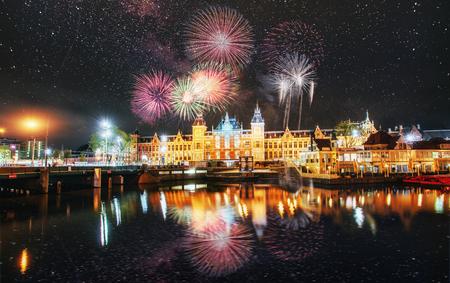 Mooie kalme nachtmening van de stad van Amsterdam. Kleurrijk vuurwerk op de zwarte hemelachtergrond. Foto wenskaart. Bokeh lichteffect, zacht filter.