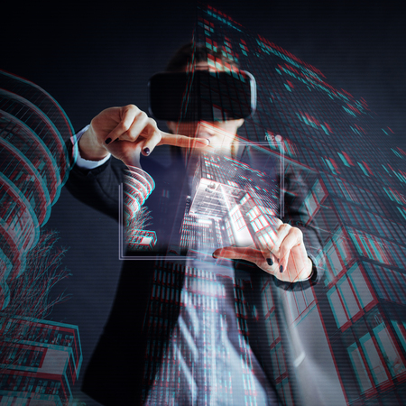 Young girl getting experience VR headset, is using augmented reality eyeglasses, being in a virtual reality. In city at night