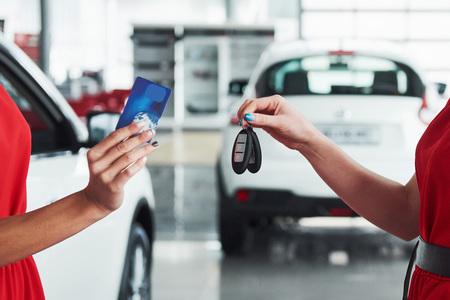 自動車ビジネス、車販売、取り引き、ジェスチャーと人々 の概念 - モーター ショーやサロンの新しい所有者にキーを与えてディーラーのクローズ