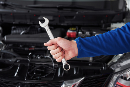 garage: Hands of car mechanic with wrench in garage.