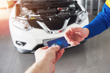 garage: Hands of car mechanic with wrench in garage, payment by credit card