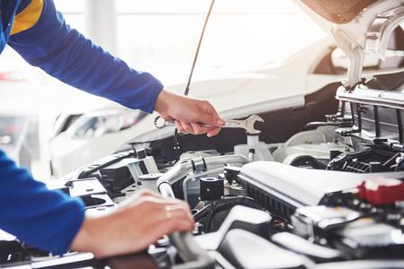 ガレージにレンチを使用して車のメカニックの手。 写真素材