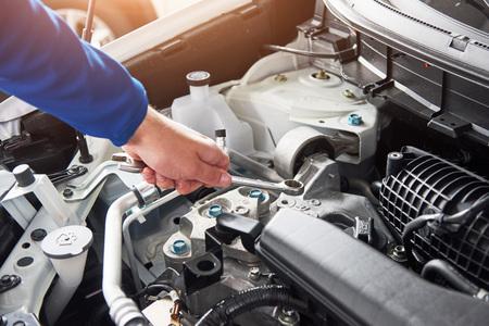 Handen van automonteur met moersleutel in garage. Stockfoto