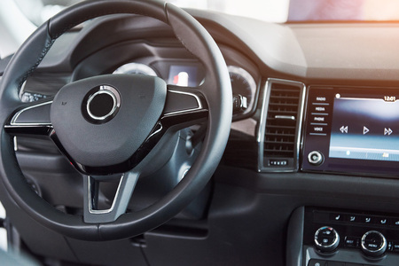 Luxury car Interior - steering wheel, shift lever, dashboard and computer. Фото со стока