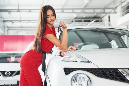 Lächelnder Autoverkäufer, der Ihre Neuwagenschlüssel, Verkaufsstelle und Verkaufskonzept überreicht. Glückliches Mädchen der Käufer Standard-Bild - 86032930