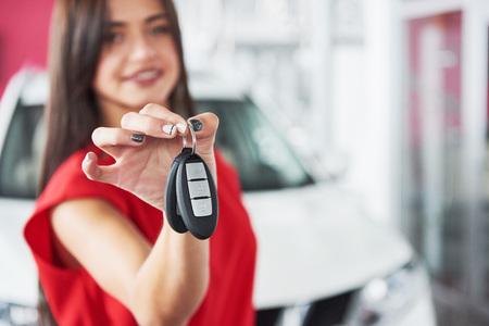 Lächelnder Autoverkäufer, der Ihre Neuwagenschlüssel, Verkaufsstelle und Verkaufskonzept überreicht. Glückliches Mädchen der Käufer Standard-Bild - 86032931