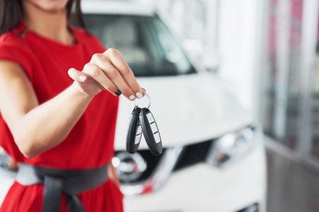 Lächelnder Autoverkäufer, der Ihre Neuwagenschlüssel, Verkaufsstelle und Verkaufskonzept überreicht. Glückliches Mädchen der Käufer Standard-Bild - 85894886