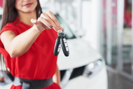 Lächelnder Autoverkäufer, der Ihre Neuwagenschlüssel, Verkaufsstelle und Verkaufskonzept überreicht. Glückliches Mädchen der Käufer Standard-Bild - 85894887