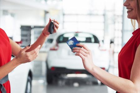 Lächelnder Autoverkäufer, der Ihre Neuwagenschlüssel, Verkaufsstelle und Verkaufskonzept überreicht. Glückliches Mädchen der Käufer Standard-Bild - 85949248