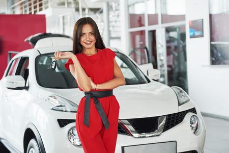 귀하의 새 차 열쇠, 딜러 및 판매 개념을 나눠주고 웃는 차 세일즈 맨. 행복한 소녀 구매자