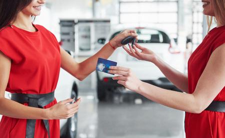 Lächelnder Autoverkäufer, der Ihre Neuwagenschlüssel, Verkaufsstelle und Verkaufskonzept überreicht. Glückliches Mädchen der Käufer Standard-Bild - 85894891