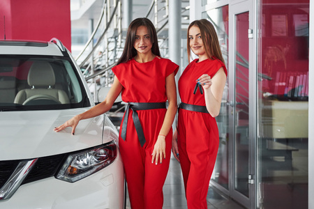 garage: Young happy two woman near the car with keys in hand - concept of buying car Stock Photo