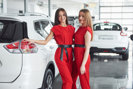 Young happy two woman near the car with keys in hand - concept of buying car Stock Photo